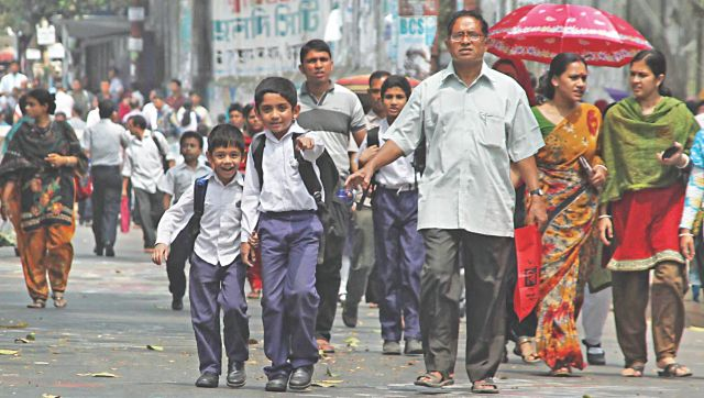 Parents take their children to school on foot yesterday at Jamal Khan area of Chittagong. The port city had a ban on public gatherings but law enforcers did not let any vehicles ply the Jamal Khan road. Photo: Anurup Kanti Das