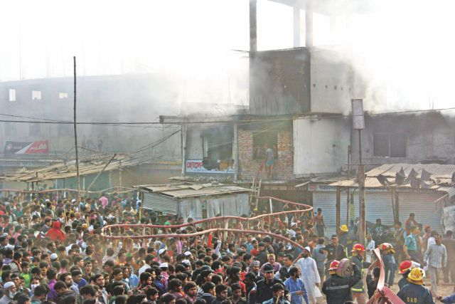People try to extinguish a fire that broke out at a factory of Smart Export Garments at Mohammadpur in Dhaka on January 26. Photo: Star/FILE