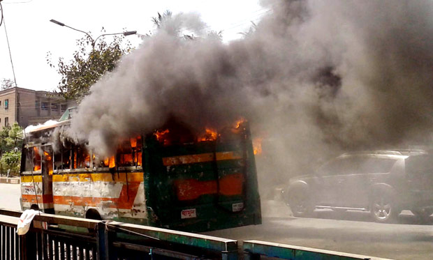 A bus burns near City College on the Mirpur Road in the capital Tuesday morning after miscreants set it ablaze on the eve of a 36-hour countrywide shutdown that begins at 6:00am Wednesday. Photo: Focus Bangla