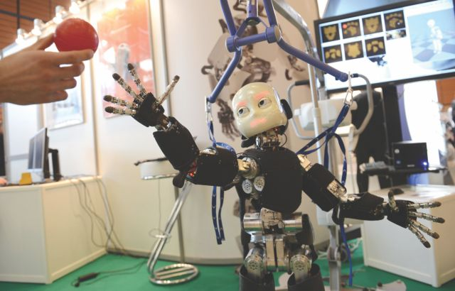 Icub, a Humanoid robot, tries to grab a ball at the Innorobo 2013 European summit in Lyon, southeastern France. Photo: AFP