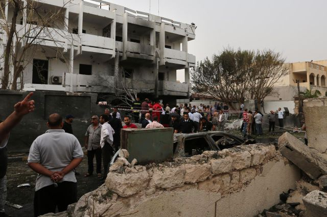 Libyan security forces gather outside the French embassy building in Tripoli following a car bomb attack yesterday. Photo: AFP