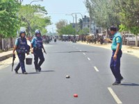 cops are seen coming with a plastic bucket to recover two cocktails lying on the road at Dingadoba intersection in Rajshahi city during the daylong shutdown enforced by Jamaat's student wing Islami Chhatra Shibir in 16 districts of Rangpur and Rajshahi divisions yesterday, demanding immediate release of its central president Delwar Hossain. Photo: Star