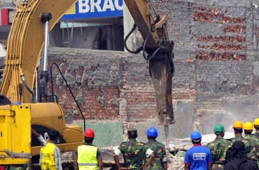This Monday photo shows rescuers using a crane to remove heavy concrete slabs of the collapsed building at Savar. Photo: STAR