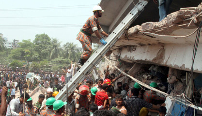 Curious people and relatives of the trapped gather as rescuers try to help out the trapped after an eight-storied building housing four garment factories in Savar collapsed Wednesday morning, Bodies of at least 10 people have been recovered and 300 have been learnt to be hurt. Photo: Palash Khan