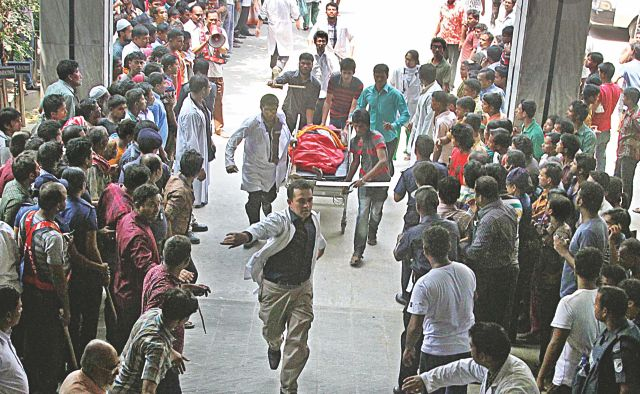 Onlookers give away as an injured of the Rana Plaza collapse is rushed into Enam Medical College Hospital in Savar yesterday. Photo: Palash Khan