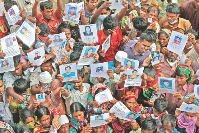 Relatives of victims yet to be rescued or recovered hold their photos high at Adhar Chandra High School playground in Savar so that rescuers who are bringing in bodies can identify them. Photo: Sk enamul haq