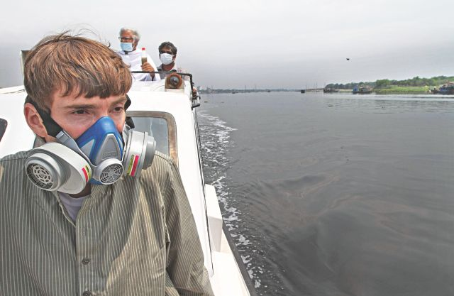 With the unbearable stench all around, Charles Depman, Asia regional coordinator of Waterkeeper Alliance, has to wear a gasmask as he takes a tour of the Buriganga near Basila yesterday. Photo: Palash Khan