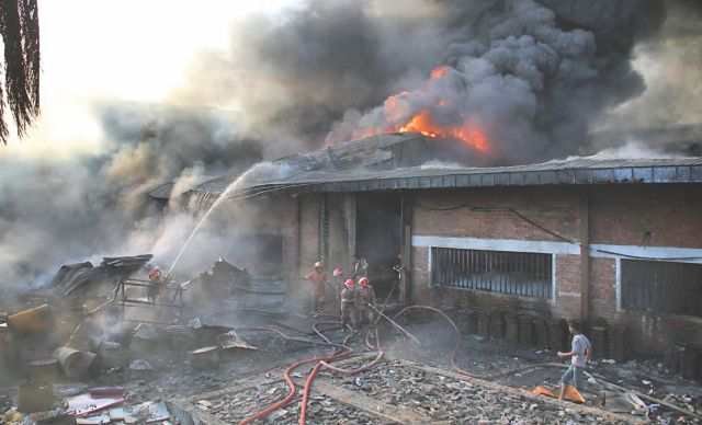 Firemen try to douse the blaze at a shoe factory in Chittagong Export Processing Zone yesterday. Photo: Star