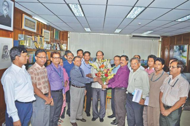 Colleagues congratulate Bangladesh Bank Governor Atiur Rahman at his office in Dhaka yesterday, as the government extended Rahman's tenure until August 2, 2016. Photo: BB
