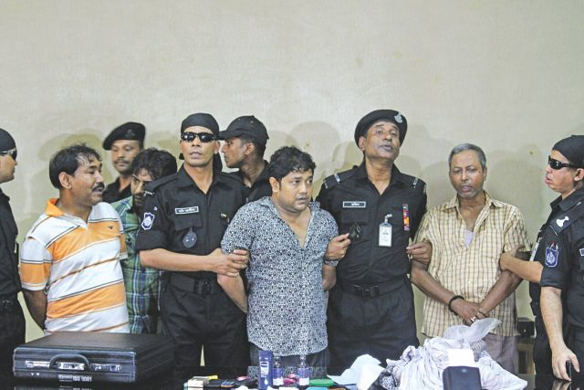 Rana Plaza owner Sohel Rana, centre, and two of his alleged aides paraded before journalists at Rab headquarters in the capital  yesterday after his arrest at Benapole trying to cross the border. Photo: Palash Khan