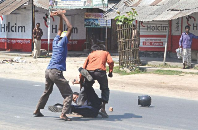 A Shibir activist bashes the cop's head with a brick.