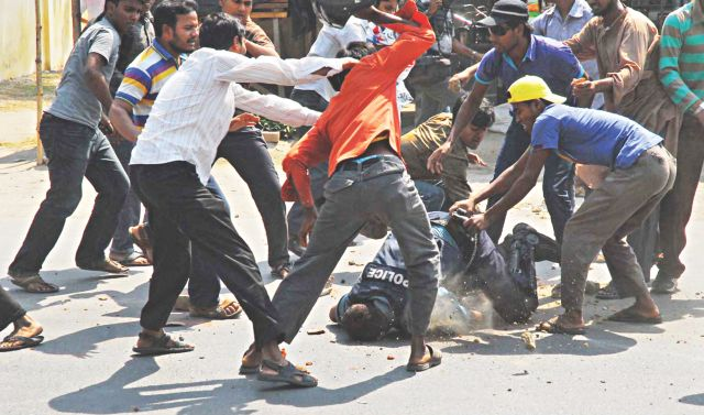 A swarm of Islami Chhatra Shibir cadres attacks police officer Jahangir Alam during a clash at Shalbagan of Rajshahi yesterday and one of them tries to get his sidearm out of its holster. Photo: Star/Focus Bangla