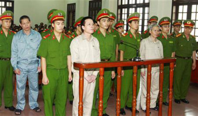 Doan Van Vuon (standing, 4th L), Doan Van Quy (standing, 2nd L) and Doan Van Sinh (standing, 3rd R) stand with policemen in front of the dock at a court during a verdict session in Hai Phong, 100 kilometres east of Hanoi, April 5, 2013, in this picture provided by the Vietnam News Agency. Photo: Reuters