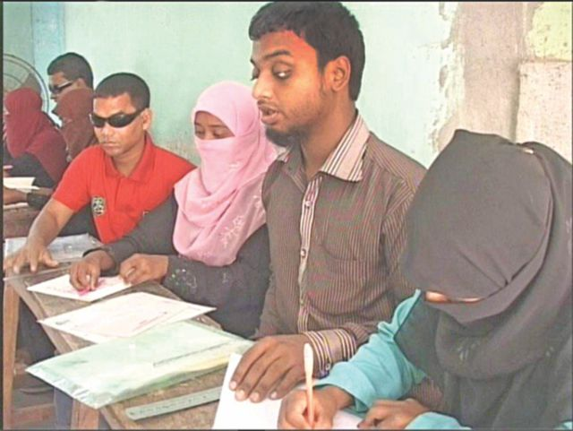 Visually impaired candidates appear at yesterday's HSC examination at Pabna Government Women's College centre with the help of persons writing the answer scripts from dictation.   PHOTO: STAR