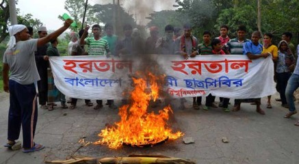After setting fire to a tyre, pro-hartal activists stand with a banner supporting hartal (Shutdown) on a road at Kharkhari in Rajshahi city during a dawn-to-dusk hartal enforced by BNP led 18-party alliance. Photo: STAR