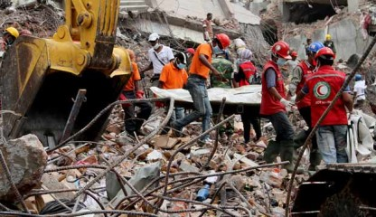 In this May 4 photo, rescuers are seen taking a body recovered from the rubble of the collapsed Rana Plaza at Savar, an outskirt area of the capital.
