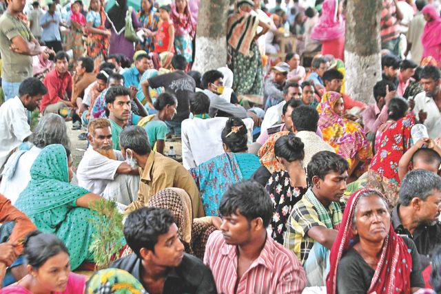 A few hundred people wait at Adhar Chandra High School playground in Savar for the bodies of their loved ones who have been missing since the Rana Plaza came crashing down on April 24. Photo: Anisur Rahman