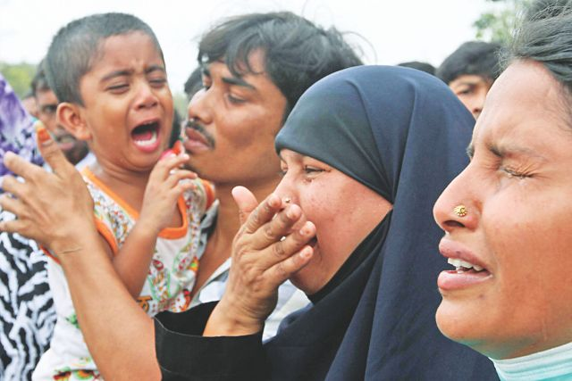 A woman along with her son and relatives cries her heart out in front of collapsed Rana Plaza in Savar yesterday. Shariful Islam, her husband, is one of those ill-fated workers who were in the building when it caved on April 24. Photo: Anisur Rahman
