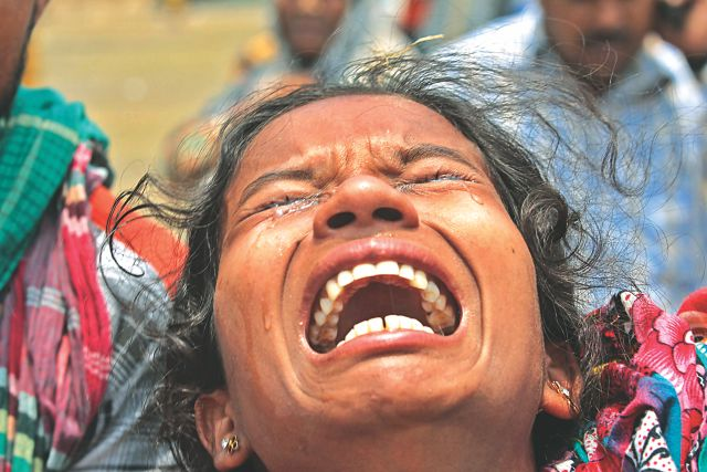 Shefali in agony after her sister Rezia's body was brought to Adhar Chandra High School playground in Savar yesterday. Shefali along with her three sisters worked in Rana Plaza and all but Rezia escaped alive. Photo: Sk Enamul Haq
