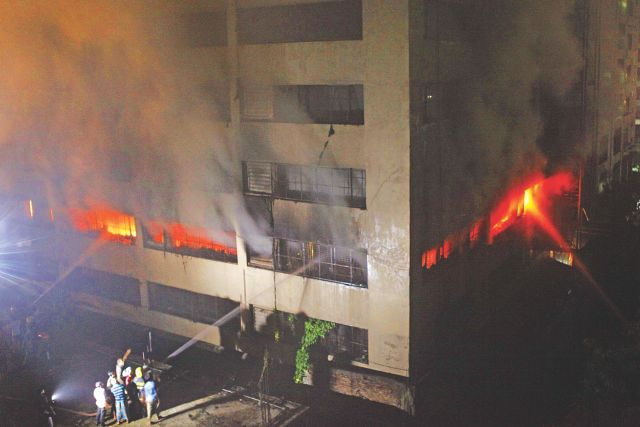 Fire fighters try to douse a blaze at a garment factory on the third floor of an 11-storey building in Mirpur Darussalam area early today. The fire broke out at Tung Hai Sweater Ltd yesterday around 11:05pm.Photo: Rashed Shumon