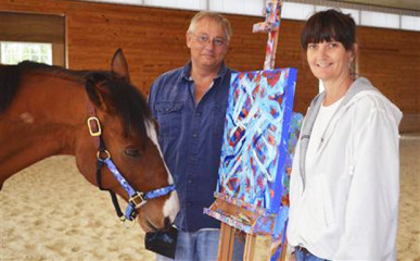 Metro, a 10-year-old retired bay thoroughbred horse stands with owners Ron Krajewski and Wendy Krajewski (R) and one of his paintings at Motter's Station Stables in Rocky Ridge, Maryland May 2, 2013. Since giving up the track, Metro has begun a successful painting career that has netted about $20,000 in four months. Photo: Reuters