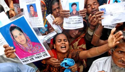 This Thursday photo shows relatives of missing Savar victims holding photos of their near and dear ones on ninth day after the Rana plaza collapsed. The death toll rises to 501 on Friday noon.