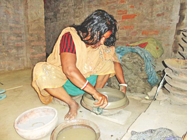 Two potters giving final touches to their items at Baroghoria Chunaripara village in Chapainawabganj Sadar upazila. However, uncertainty has gripped the traditional cottage industry due to falling demand of earthenware. PHOTO: STAR