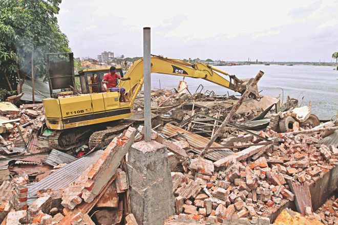 A bulldozer demolishing structures on the encroached upon land of the Turag river in Ramchandrapur of the capital's Mohammadpur. The drive was jointly carried out on Monday by Bangladesh Inland Water Transport Authority and the Dhaka district administration. Photo: Star