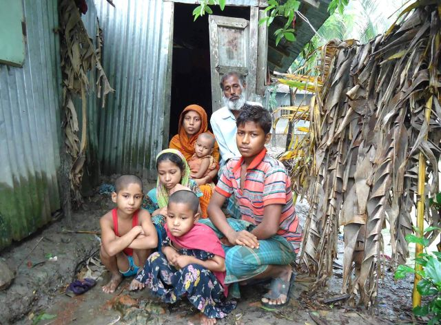 With a deep sense of despair, day labourer Sattar Matabbar along with his family members sits in front of a slum in Patuakhali town. A gang grabbed his homestead at Rajnagar village in Baufal upazila of the district on Wednesday. Photo: Star