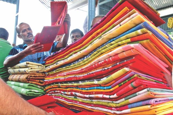 A trader takes a look at a Jamdani sari at a bazaar in Demra on the outskirts of the capital yesterday.  Photo:Star