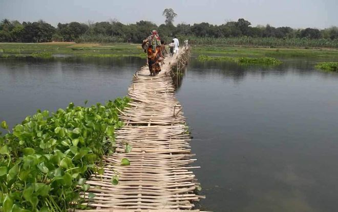 People use this rickety bamboo bridge to cross the Kumar River at Aruakandi in Shailkupa upazila under Jhenidah district as their demand for construction of a concrete bridge there has remained unheeded for long.  PHOTO: STAR