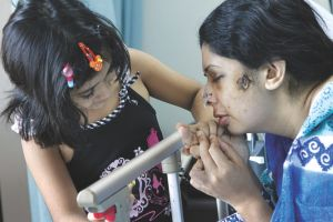 Rumana with her child at a Dhaka hospital after she was assaulted by her husband in June 2011.  File photo