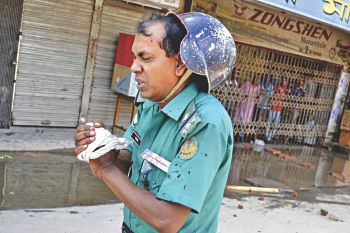 Nazrul Islam, assistant sub-inspector of Boalia Police Station, suffered splinter injuries in the left hand in a sudden cocktail attack by Islami Chhatra Shibir activists while his team was patrolling Ranibazar area of Rajshahi city yesterday. He was treated in Rajshahi Medical College Hospital. Photo: Star
