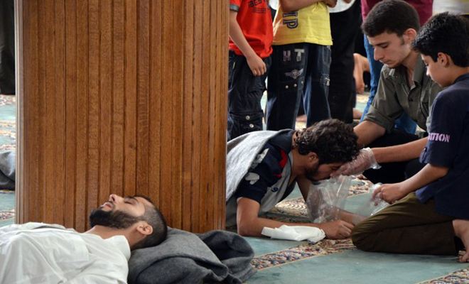 A survivor from what activists say is gas attack vomits inside a mosque in the Duma neighbourhood of Damascus August 21. Photo: Reuters