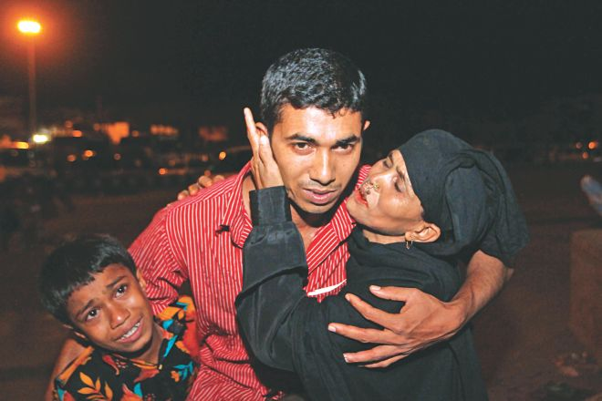Overseas jobseeker Nur-e-Alam is hugged by his crying mother Shahnoor Begum and son Russell at Shahjalal International Airport late Sunday night. Alam returned from Egypt empty handed as he was cheated by brokers who sent him abroad on a tourist visa. Photo: Palash Khan