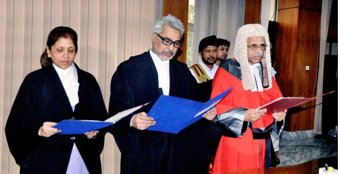 Chief Justice Md Muzammel Hossain administers oath to two newly appointed additional judges of the High Court -- Md Shahinur Islam and Kashifa Hossain -- at the judges' lounge of the Supreme Court yesterday.   Photo: PID