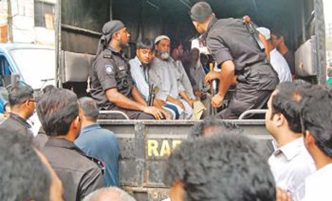 In this September 28 photo, Rab personnel are seen detaining drug traders during a raid at Mitford. Photo: Banglar Chokh