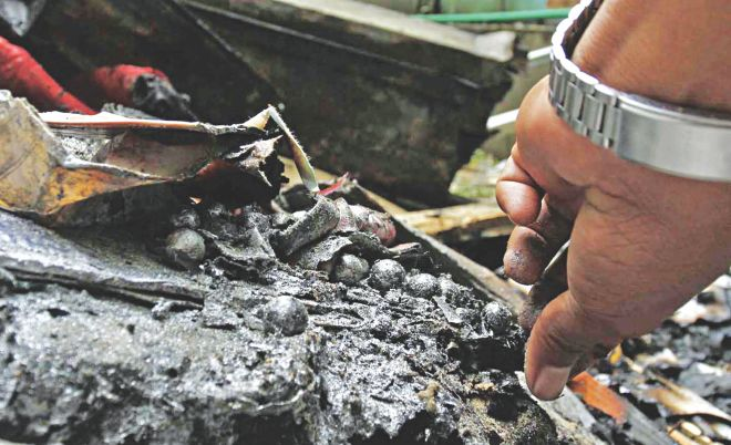 A law enforcer picks up marbles, sometimes used as shrapnel in home-made bombs, from the debris of an explosion at a madrasa in Lal Khan Bazar in Chittagong yesterday. Photo: Anurup Kanti Das