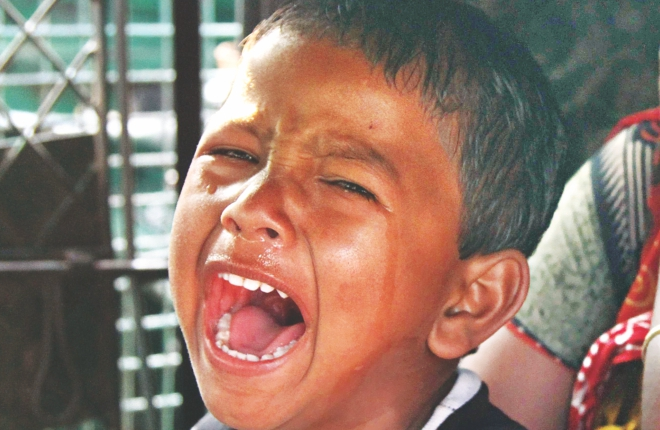 Arif, 3, the son of auto rickshaw driver Sabed Ali, top, cries his heart out after seeing his father burnt and bandaged at the burn unit of Dhaka Medical College Hospital. Alleged opposition activists hurled a petrol bomb at Sabed's vehicle in front of Eastern Plaza during the opposition enforced nationwide blockade yesterday. Photo: Amran Hossain