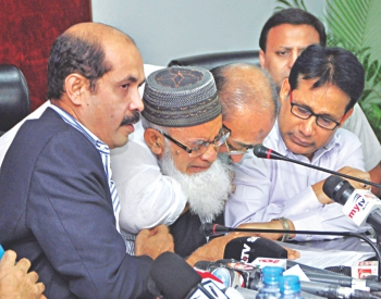Fellow garment factory owners hold Standard Group Managing Director Mosharraf Hossain, who breaks down in tears during a press conference at the BGMEA Bhaban yesterday afternoon. Mosharraf lost six factories to arson on Friday.Photo: Palash Khan/ BGMEA